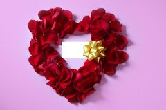 Red rose petals in heart shape Stock Images