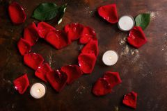 Red rose petals in heart shape with white candles on dark brown and golden background. Love, romance, anniversary, valentine`s day Stock Photo