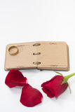 Red rose petals with opened antique diary and golden ring Royalty Free Stock Image