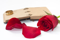 Red rose petals with opened antique diary and golden ring Stock Image