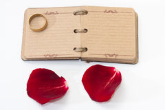 Red rose petals with opened antique diary and golden ring Royalty Free Stock Photo