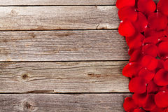 Red rose petals over wooden background Royalty Free Stock Photo
