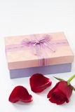 Red rose petals with pink gift box with a bow Royalty Free Stock Photos
