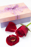 Red rose petals with pink gift box with a bow and golden ring Stock Photos
