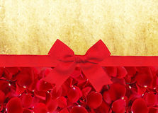 Red rose petals and red ribbon with bow over old paper Royalty Free Stock Photo