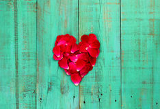 Red rose petals in the shape of a heart on distressed antique teal blue wood door