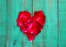 Red rose petals in the shape of heart on distressed antique teal blue wood door Royalty Free Stock Photography