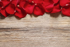 Red rose petals on wooden background Stock Image