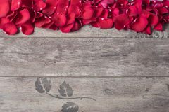 Red rose petals on the wooden background. Rose Petals Border on a wooden table. Top view, copy space. Floral frame. Stock Image