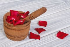 Red rose petals in a wooden mortar Royalty Free Stock Image