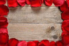 Red rose petals on wooden table Stock Photography