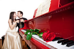 Red rose on piano. Red rose on the red grand piano keyboard in focus and couple sitting on the chair with glasses of wine at background Stock Images