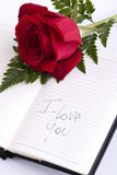 Red rose on planner. I love you writte on it Stock Photos