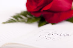 Red rose on planner. I love you writte on it Royalty Free Stock Photos