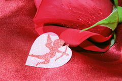 Red Rose. A pretty red rose with a sparkling cupid on silky red sheets stock photo