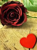 Red rose and red heart on a wooden table Royalty Free Stock Photo