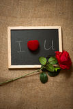 Red rose and ring in box lying on chalkboard Stock Photo