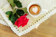 Red rose on the rough table napkin with cup of coffe.Wooden tabl Stock Photo