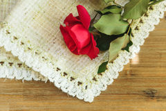Red rose on the rough table napkin.Wooden table background.Top v Stock Photography