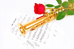 Red rose, saxophone and music sheet. On a white background Stock Images