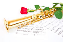 Red rose, saxophone and music sheet. On a white background Royalty Free Stock Photos