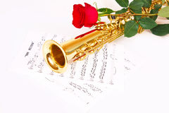 Red rose, saxophone and music sheet. On a white background Stock Photography