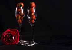 Red rose and strawberries. Two crystal champagne flute glasses filled with strawberries and single red rose, isolated on black background Royalty Free Stock Image
