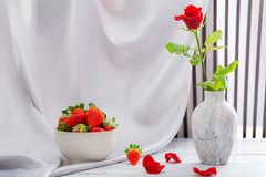 Red rose, strawberries. And champagne for the celebration of women`s holidays and anniversaries stock photo