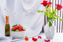 Red rose, strawberries and champagne for the celebration of women`s holidays and anniversaries. Red rose, strawberries and champagne happy birthday set royalty free stock photos