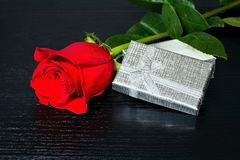 Red rose with surprise in a box on the luxury wooden table. For lovers. Rose and gift on the wooden table. Stock Photo