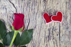 Red rose with two hearts on o;d textured wood for valentine`s da Royalty Free Stock Photo