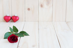 Red rose and two hearts on wooden background Royalty Free Stock Images