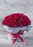 Red roses. Red rose in a vase on a wooden background Royalty Free Stock Image