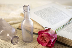 Red Rose and Vintage Apothecary Bottles. A single red rose laying on top of an opened vintage book with a couple of vintage apothecary bottles Stock Photography