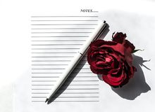 Red rose on white background. Notepad and pen Royalty Free Stock Photo