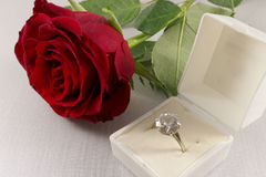 Red rose and white box with golden engagement ring Stock Photo