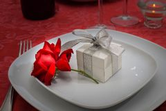 A red rose with a white box with a silver ribbon Stock Photo