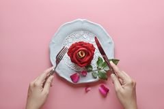 Red rose on white dish, Couple ring inside, with hand holding fork and knife, on pink background, Concept of Valentine`s Day stock image