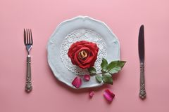 Red rose on white dish, with couple ring inside, On pink background, Concept of Valentine`s Day. Red rose on white dish, with couple ring inside, On pink royalty free stock photo
