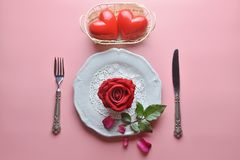 Red rose on white dish, with fork and knife, And couple heart in white basket, On pink background. stock photos