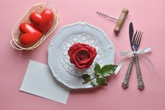 Red rose on white dish, with fork and knife in ribbon, And couple heart in white basket, Wine opener, Greeting card. royalty free stock photos