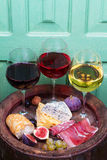 Red, rose and white  glasses and bottles of wine. Cheese, fig, grape, prosciutto and bread on old wooden barrel. Royalty Free Stock Images
