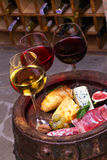 Red, rose and white  glasses and bottles of wine. Cheese, fig, grape, prosciutto and bread on old wooden barrel. Stock Images