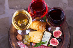 Red, rose and white  glasses and bottles of wine. Cheese, fig, grape, prosciutto and bread on old wooden barrel. View from above Stock Photos