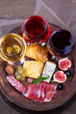 Red, rose and white  glasses and bottles of wine. Cheese, fig, grape, prosciutto and bread on old wooden barrel. View from above Royalty Free Stock Image