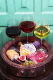 Red, rose and white glasses and bottles of wine. Grape, fig, nuts and leaves on old blue table. Stock Image