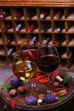 Red, rose and white glasses and bottles of wine. Grape, fig, nuts and leaves on old wooden barrel. Stock Images