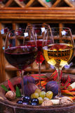 Red, rose and white glasses and bottles of wine. Grape, fig, nuts and leaves on old wooden barrel. Royalty Free Stock Image