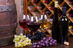 Red, rose and white glasses and bottles of wine, grape and old wooden barrel. Stock Photo