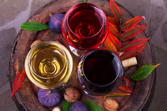 Red, rose and white glasses of wine. Grape, fig, nuts and leaves on old wooden barrel. View from above, top studio shot. Stock Photography